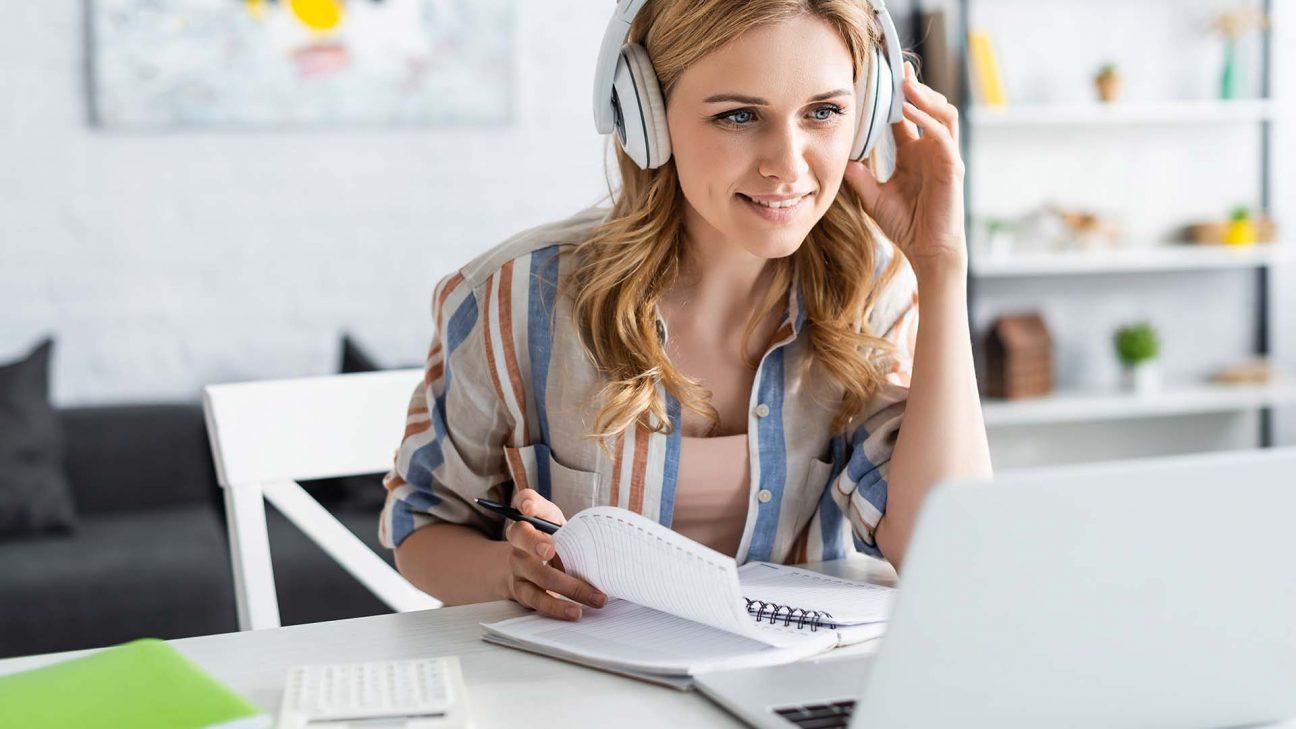 eine Frau sitzt am Schreibtisch mit Kopfhörern