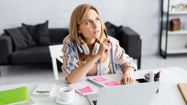 eine Frau sitzt am Schreibtisch und guckt nachdenklich