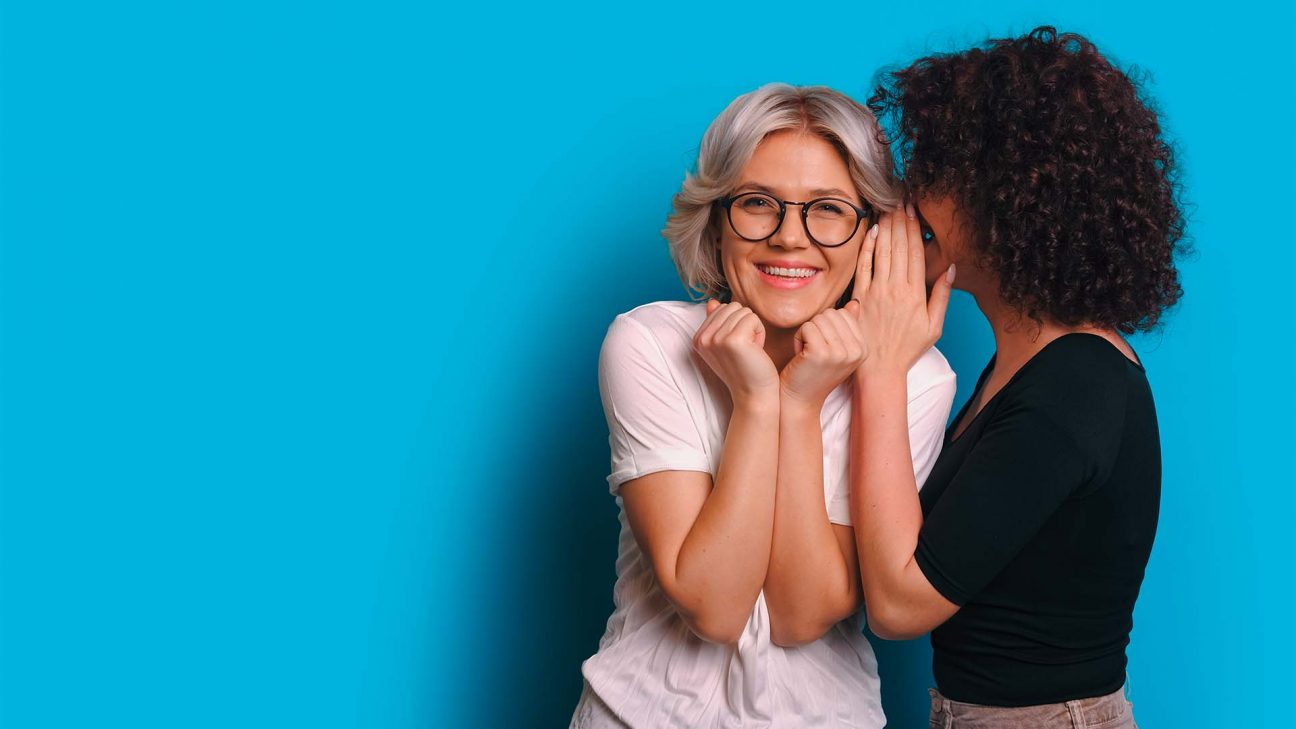 eine Frau flüstert einer anderen Frau etwas ins Ohr